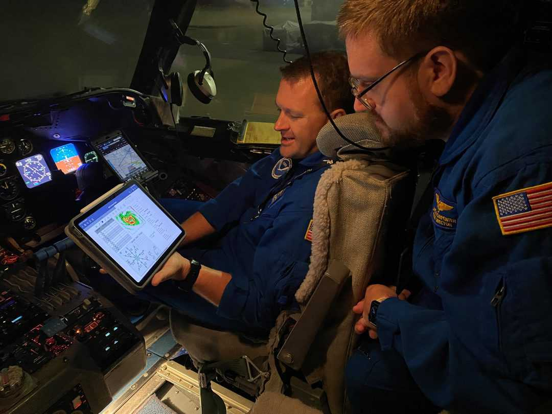 Lt. Cmdr. Mitchell discusses flight plan with Flight Director James Carpenter in flight station of NOAA WP-3D Orion N43RF Miss Piggy before an early morning mission to Hurricane Ida on August 28, 2021.